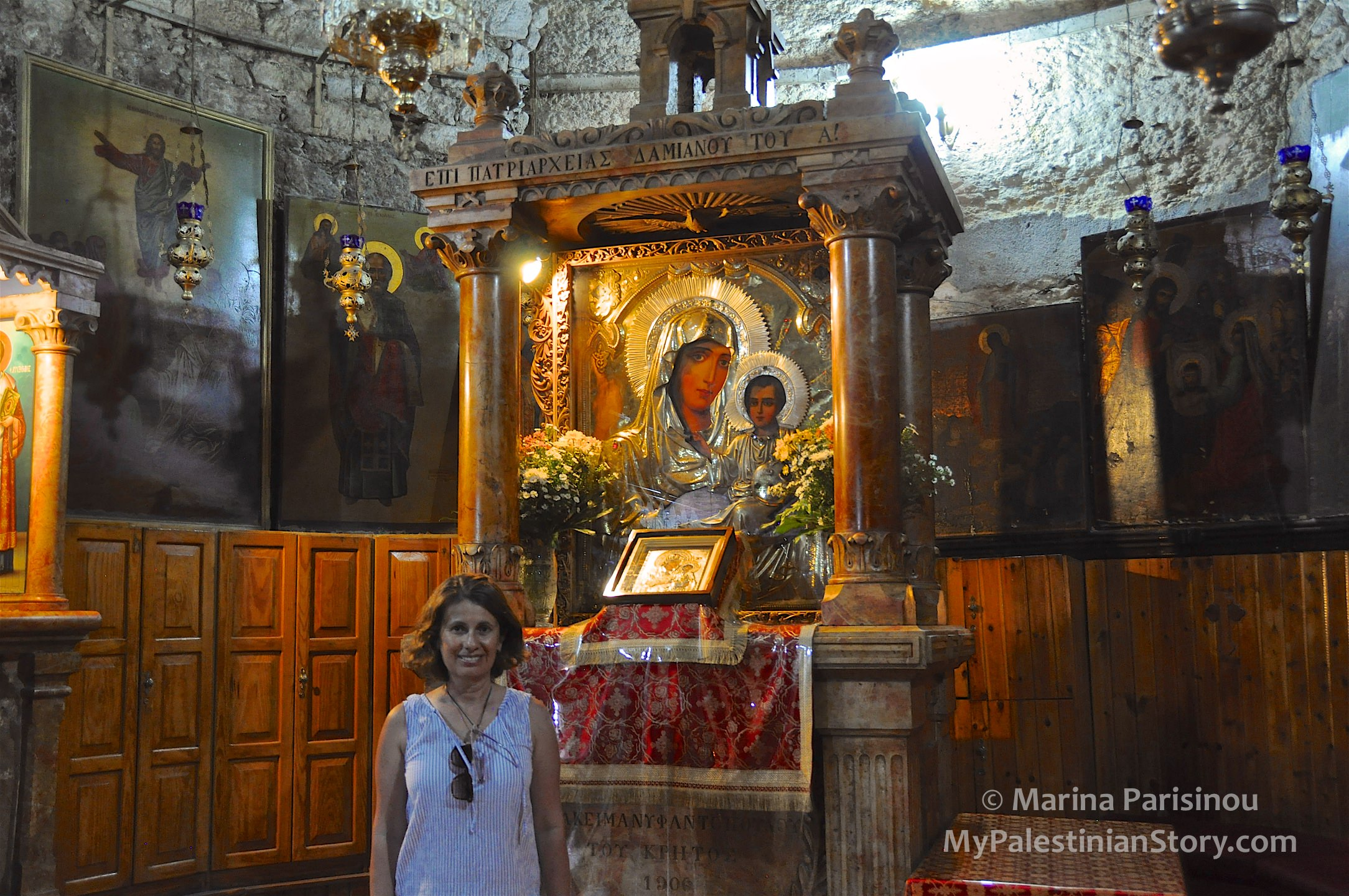 "Posing in front of the icon of Virgin Mary the Jerusalemite. The inscription at the top reads: ""During the Patriarchate of Damianos I"""